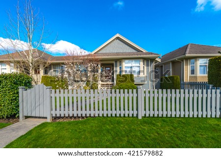 House behind country style long wooden fence with nicely trimmed grass. Spring time. - stock photo