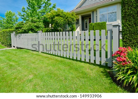 House behind county style wooden fence and nicely trimmed lawn.