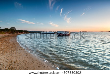 House boats on the beach at Bramble Bush Bay on Studland in Dorset - stock photo