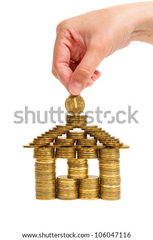 house built of coins female hand isolated on white background, front view - stock photo