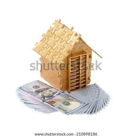 House built out of puzzle pieces with money and golden abacus - stock photo