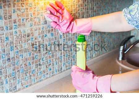 House cleaning - woman washes ceramic tiles on kitchen wall with detergent