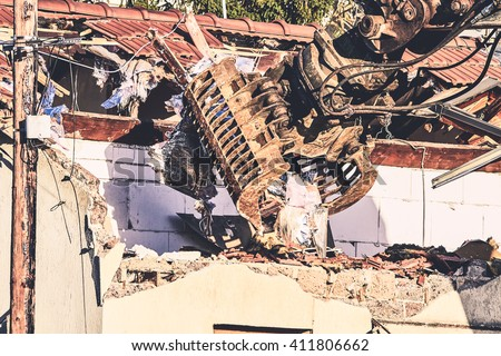 House demolition by bulldozer. Closeup of Demolition of the Old Building - stock photo