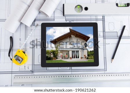 House displayed on digital tablet screen with architect's tools over blueprint - stock photo