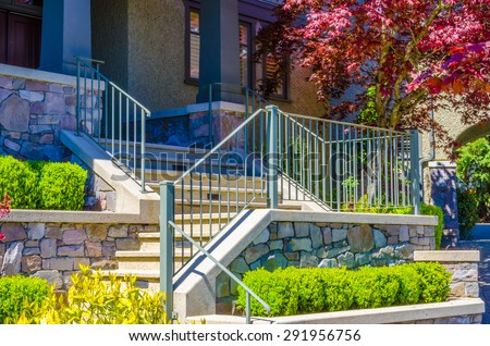 House entrance with nicely paved doorway, steps and handrails and trimmed and landscaped front yard. - stock photo