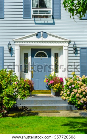 House entrance with nicely trimmed and landscaped front yard.