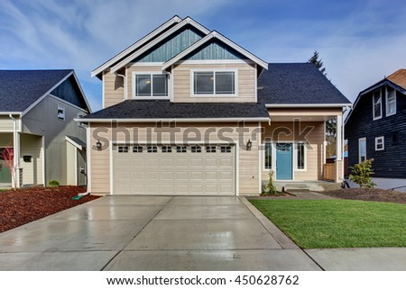 House exterior. American beige house with green grass. Garage with driveway