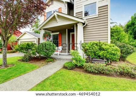 House exterior with siding trim, red entry door and concrete walkway. Northwest, USA
