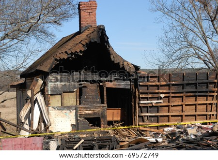 house fire damage in rural georgia usa. only thing left is the fire place in the background. total loss of home. - stock photo