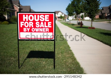 House For Sale By Owner Sign in a front yard of a home - stock photo