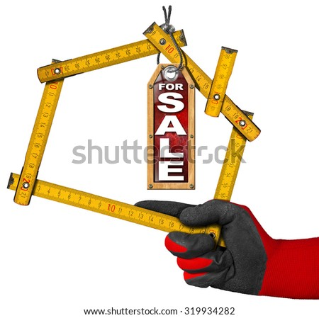House For Sale - Wood Meter Tool / Hand with work glove holding a wooden meter ruler in the shape of house with a label with text For Sale. Isolated on white background