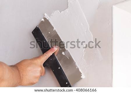 house improvement by worker puts finishing layer of stucco on the wall using a plastering trowel - stock photo