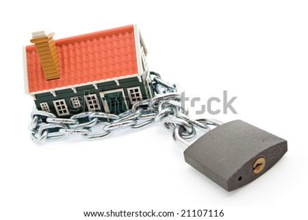 House in chains locked with padlock - mortgage and foreclosure concept - stock photo