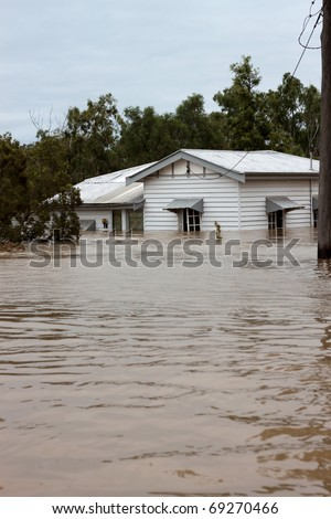 House in floodwater.  Traditional timber country home with water up the windows.  Ideal for insurance or disaster illustration. Vertical image with copy space. - stock photo
