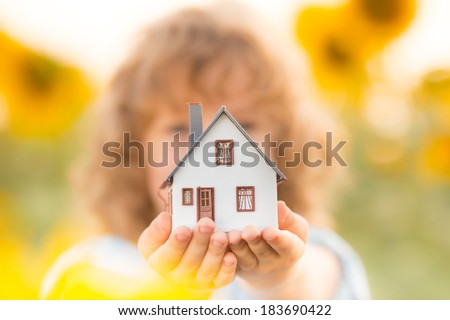 House in hand against spring green background. Real estate concept - stock photo