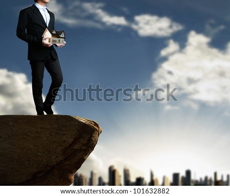 house in human hands on the cliff and down - stock photo