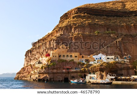 House in rock near old harbor of Thira, Santorini, Greece. - stock photo