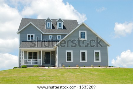 House in the Clouds - Two story house sitting on a hill. - stock photo