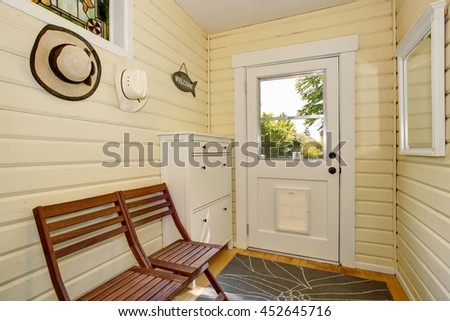 House interior. Light tones hallway with exit to backyard. Furnished with white cabinet and brown wooden chairs. - stock photo