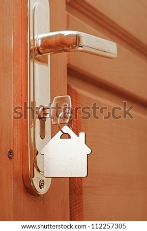 House key on a house shaped keyring in the lock of a door
