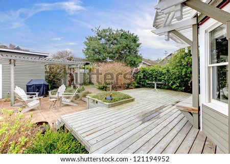 House large deck and backyard during early spring. - stock photo