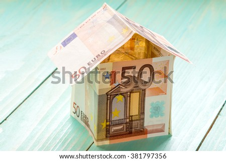 House made of Euro banknotes on a wooden background - stock photo