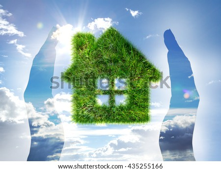 House made of grass on blue sky between hands - stock photo