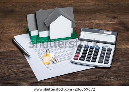 House Model On Contract Paper With Keys And Calculator Kept On Wooden Desk - stock photo