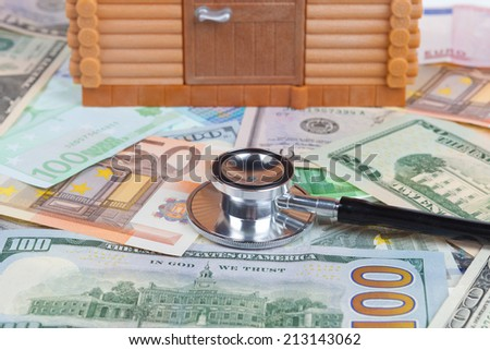 House model on money banknote with stethoscope