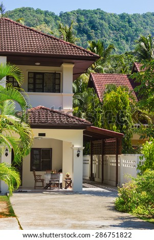 House near the mountains covered with jungle. Thailand - stock photo