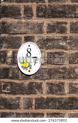 House number eighty seven mounted on a brick wall vintage look - stock photo