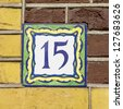 house number fifteen on a decorated ceramic tile - stock photo