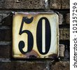 house number fifty on a rusted enameled plate - stock photo