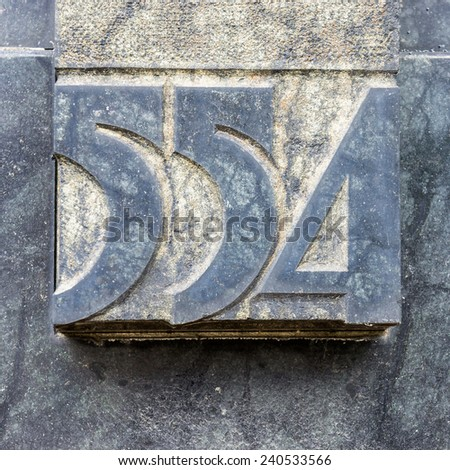 house number five hundred and fifty four, carved in natural stone - stock photo