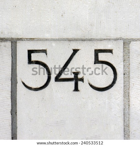 house number five hundred and forty five, carved in stone - stock photo
