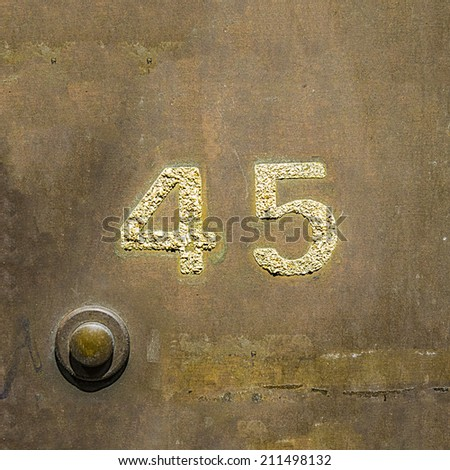 House number forty five on a copper plate next to  a door bell. - stock photo