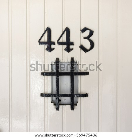 House number four hundred and forty three above a hash tag. - stock photo