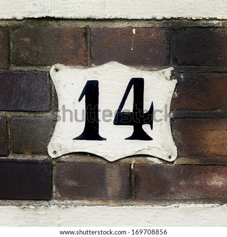 house number fourteen on a brick wall. - stock photo
