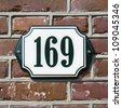 house number hundred and sixty-nine. Dark green lettering on an enameled plate - stock photo