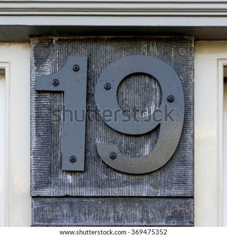 House number nineteen. Separate numerals on a stone wall - stock photo