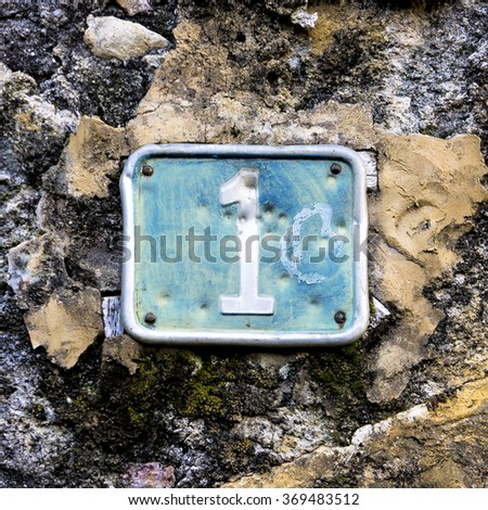 house number one, embossed in a metal plate. - stock photo