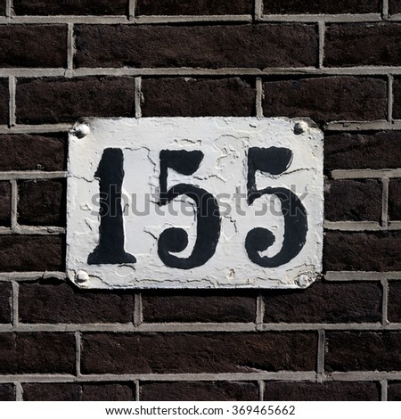House number one hundred and fifty five. Black numerals on a weathered white plate. - stock photo