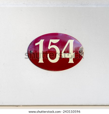 House number one hundred and fifty four on a enameled oval red plate - stock photo