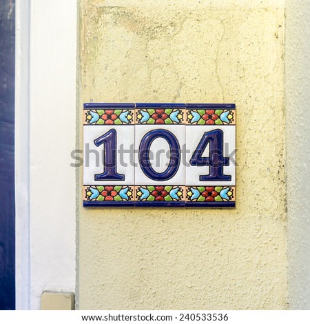 house number one hundred and four, on ceramic tiles - stock photo