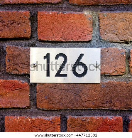 house number one hundred and twenty six (126) engraved in a stainless steel plate, - stock photo