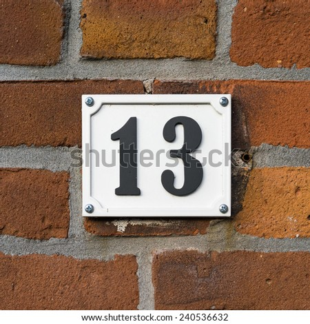 House number Thirteen. Black lettering on a white background