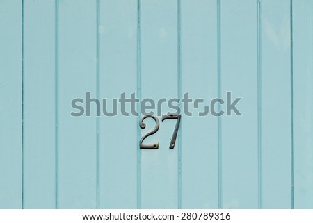 House number 27 twenety seven on a weathered blue painted metal door closeup - stock photo