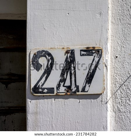 House number two hundred and forty seven. Black lettering on a white background. - stock photo