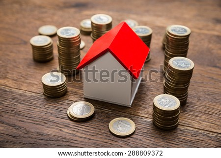 House Of Model With Coins On Wooden Table - stock photo