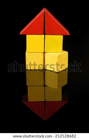 House of wooden blocks, traditional toy on black background - stock photo